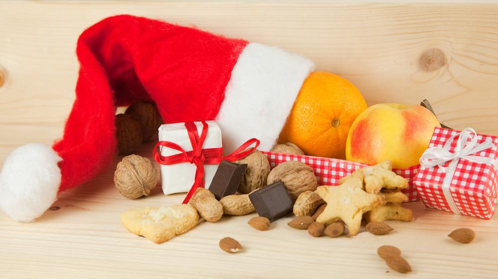 Orange, apple, chocolate, nuts, and cookies in a Santa hat