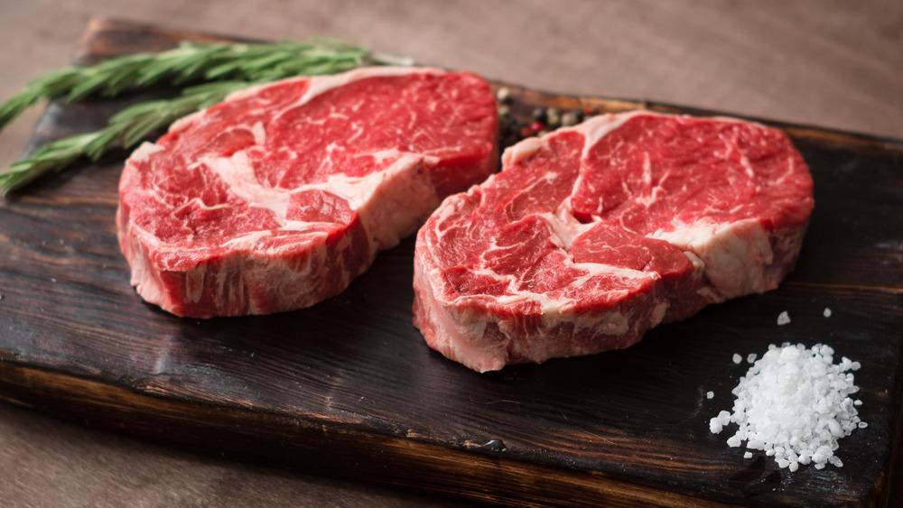 Two cuts of steak on a board