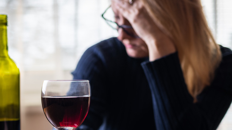 Woman with red wine and a headache