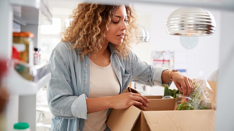 Woman with a box near her fridge