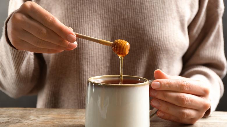 Woman putting honey in tea
