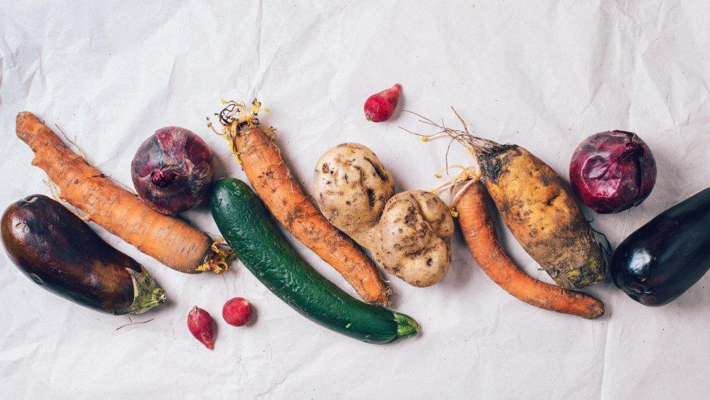 Spoiled vegetables on white background