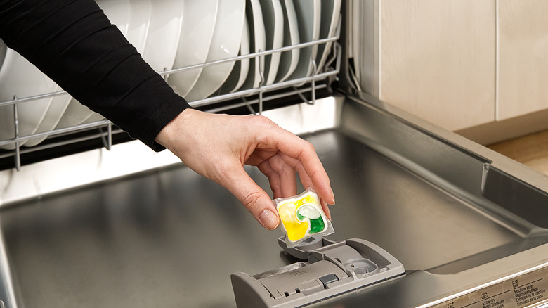 Open dishwasher with hand putting soap in slot