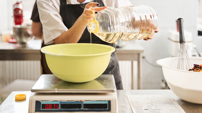 Woman pouring oil into bowl on scale