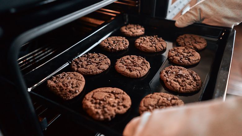 person taking cookies on a baking sheet out of the oven