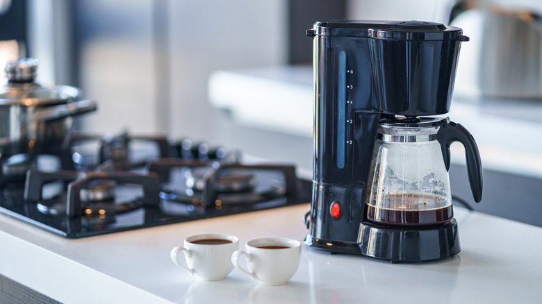Coffee maker and cups on kitchen counter