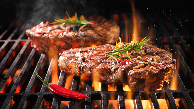 steaks on a hot grill over flame