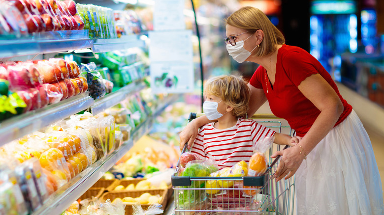 Masked woman and child grocery shopping