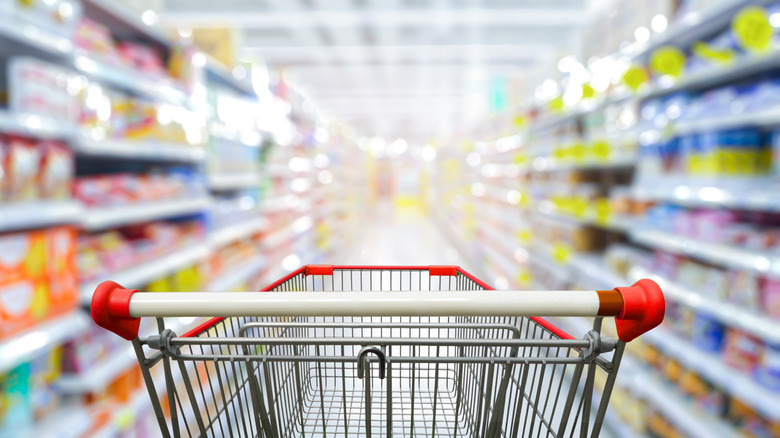 Shopping cart at the beginning of grocery store aisle