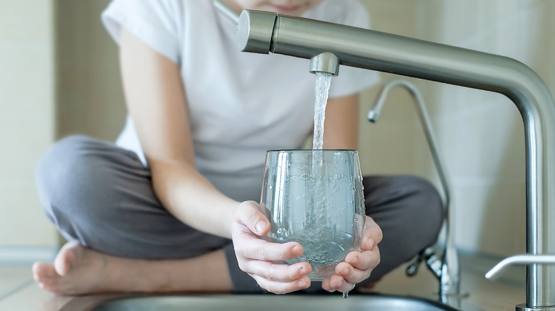 Person fills glass with tap water