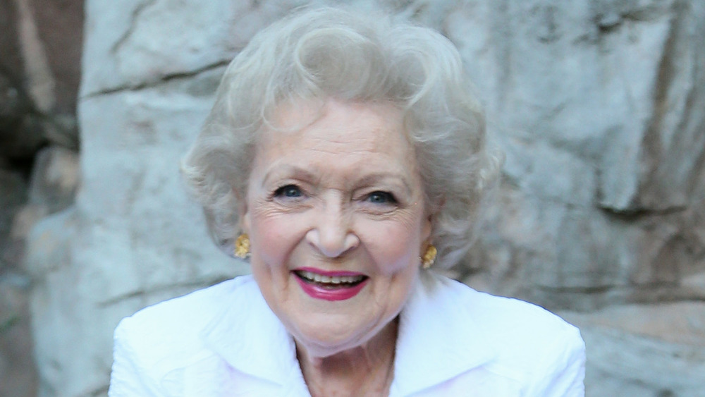 Betty White wearing gold earrings and a white blazer