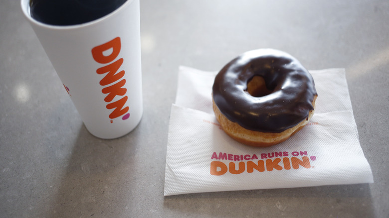 Paper cup of Dunkin' coffee and sprinkled donut