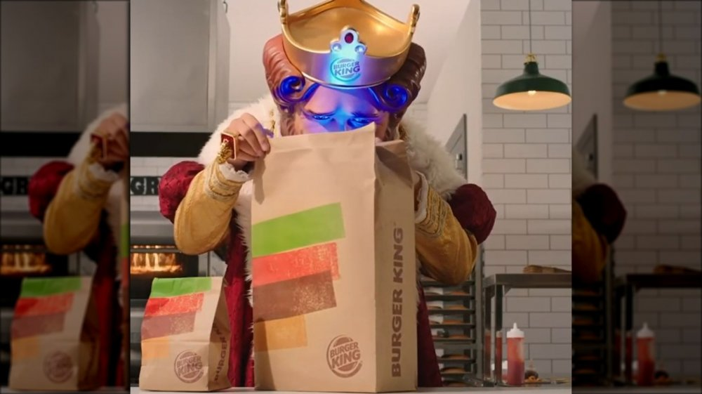 Burger King's newest ad featuring the King looking into a takeout bag. He's illuminated with a blue light