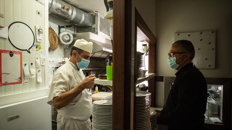 Restaurant employees interact through window