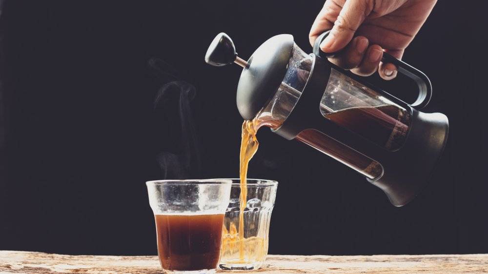 A French press pouring coffee into small glasses