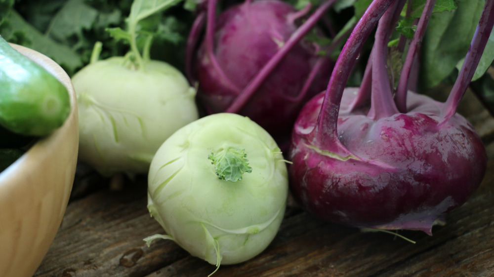 Purple and pale green kohlrabi on a wooden table