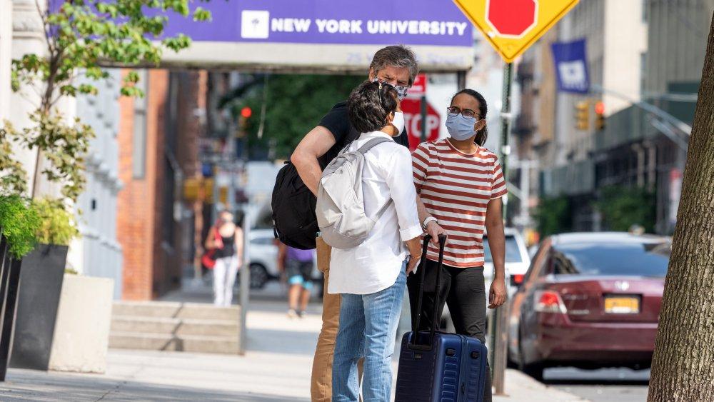 Masked NYU students gather outside of NYU building