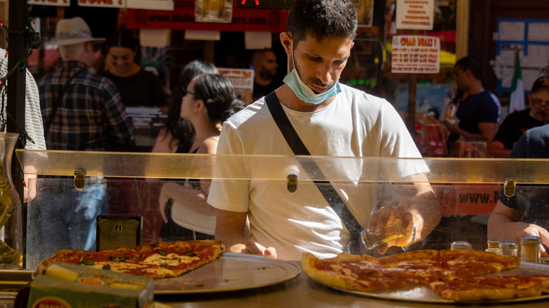A man putting toppings on a New York style pizza