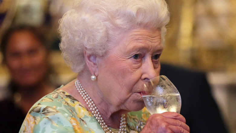 Queen Elizabeth II sipping from a glass