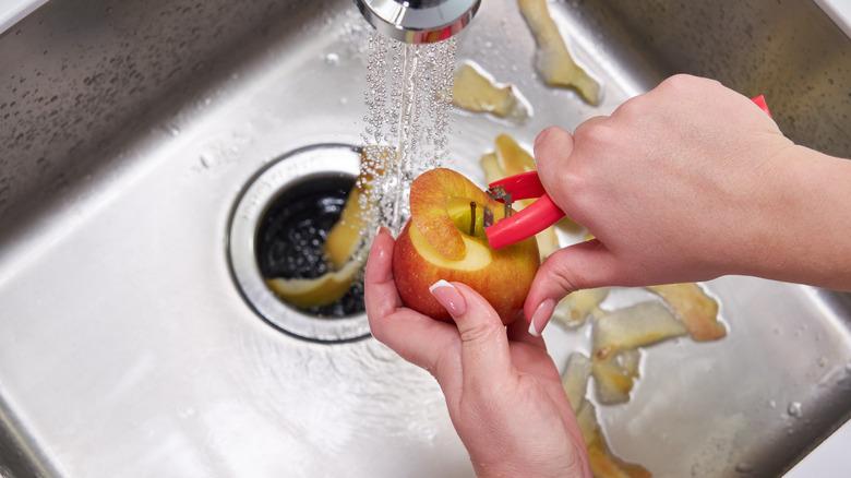 Person putting apple peel in garbage disposal
