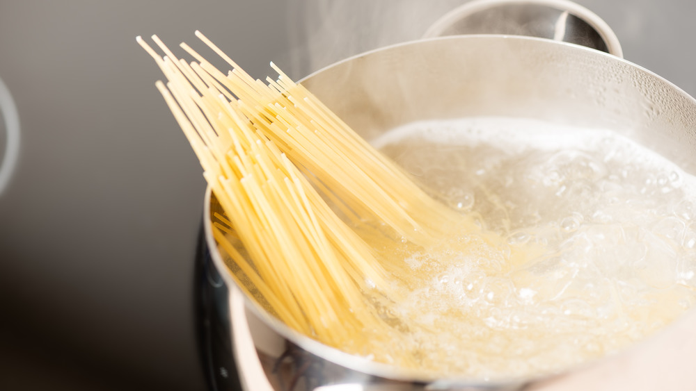 spaghetti cooking in boiling pot of water