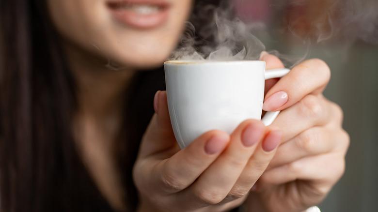 Woman holding mug of hot tea