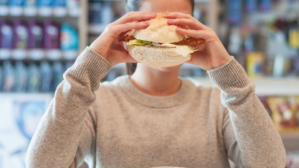 woman eating a sandwich at a gas station cafe