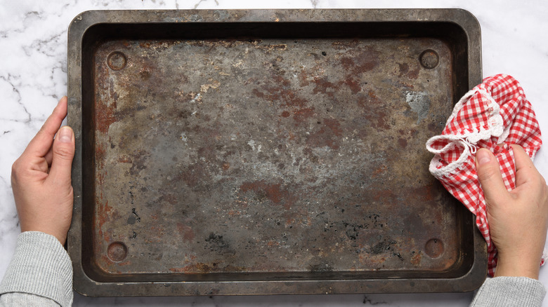 Old baking sheet in person's hands