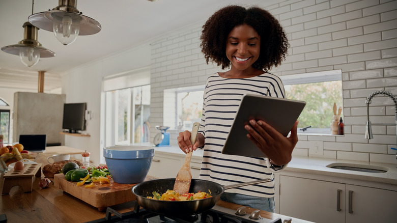 Woman looking at recipe while cooking