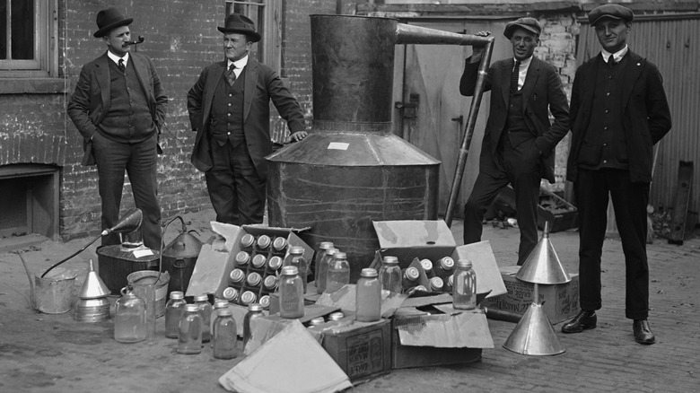 Vintage black and white photo of men in suits with boxes of bottles