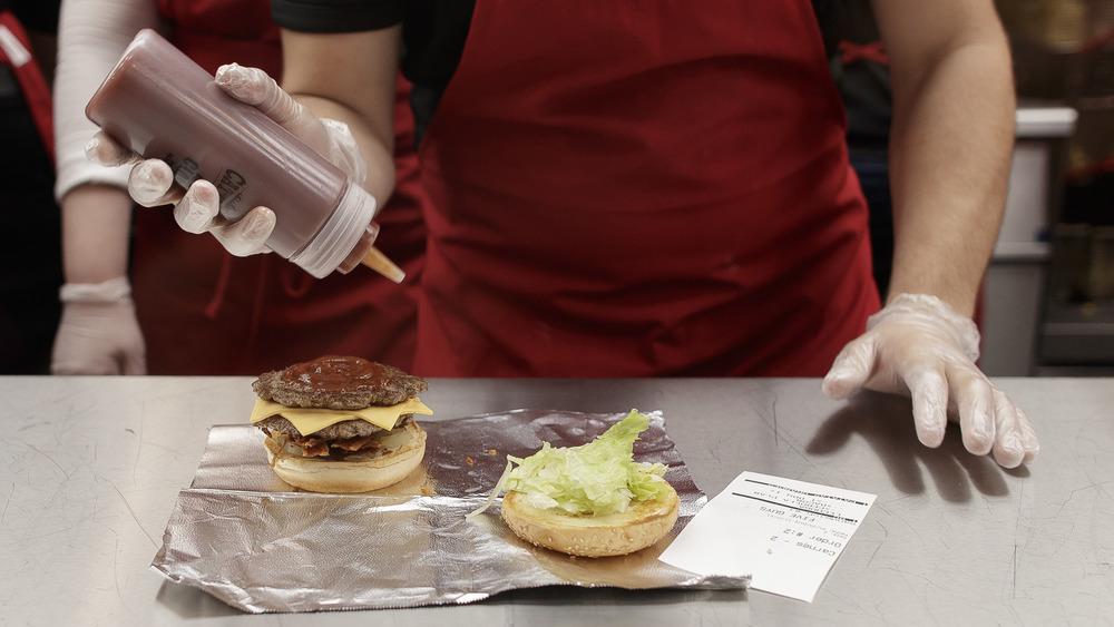 Employee making Five Guys burger