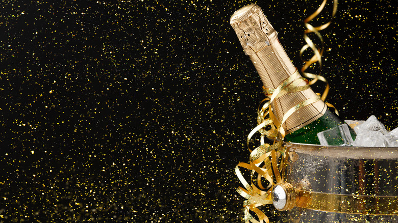 bottle of champagne in an ice bucket with glittery background