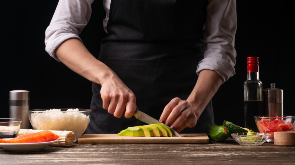 Chef cutting avocados with sushi ingredients nearby