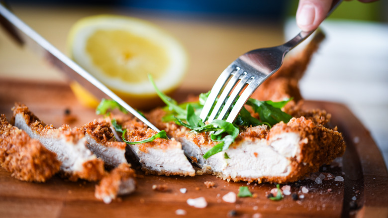 Knife and fork cutting chicken schnitzel