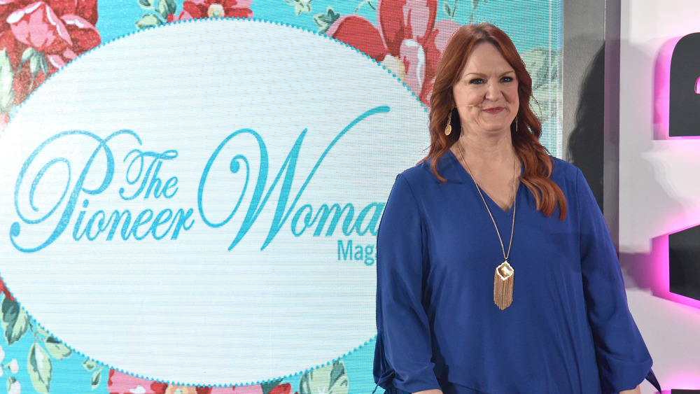 Ree Drummond standing by Pioneer Woman sign