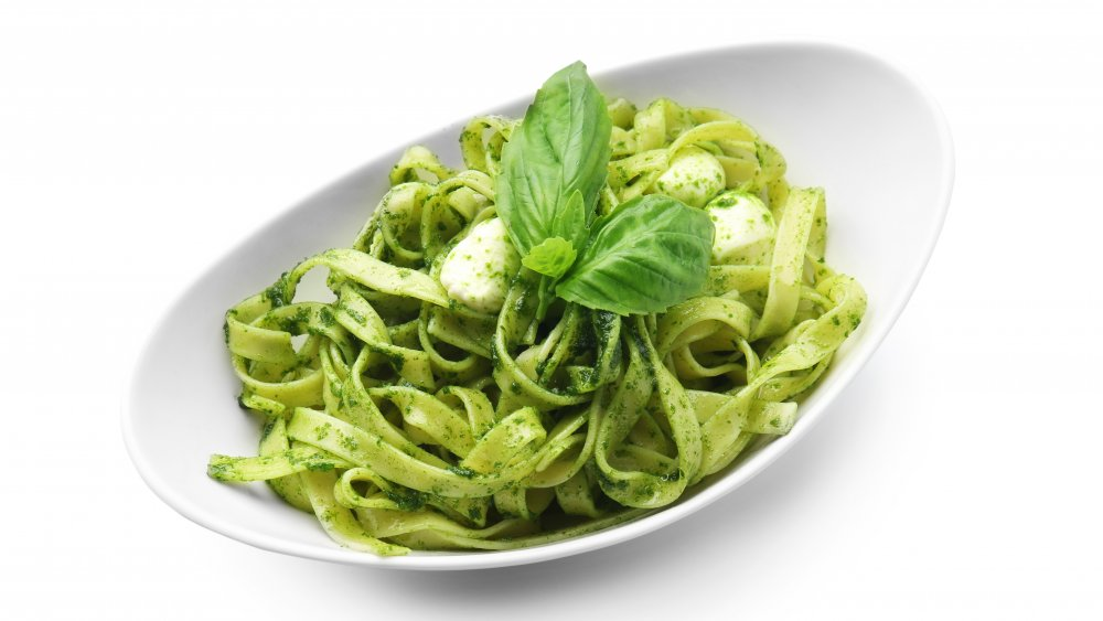 Fettuccine pasta in pesto sauce on a white background.