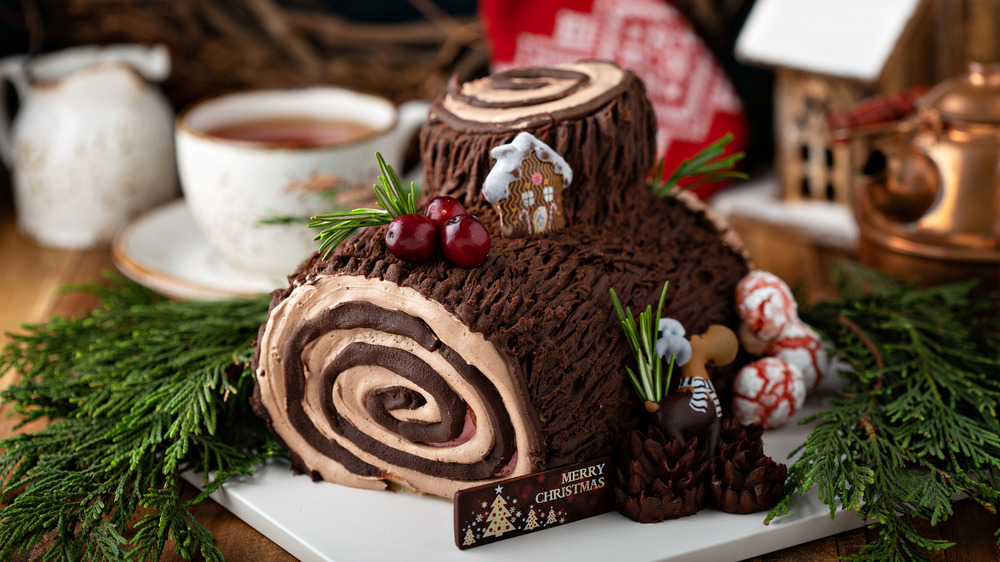Yule log, with Christmassy garnishes and coffee cup