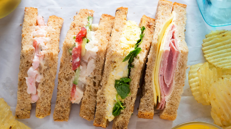Four different types of sandwiches on a tray with potato chips.
