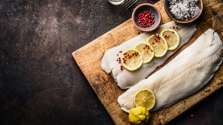 Raw white fish on wooden board with lemon and spices