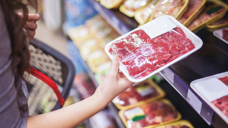 Woman buying beef at the grocery store