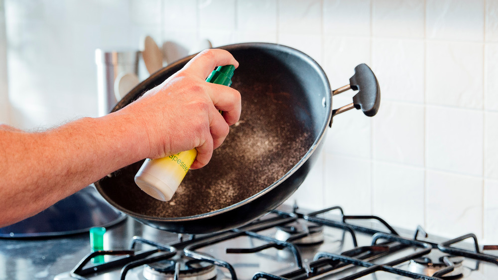Man spraying pan with oil while cooking