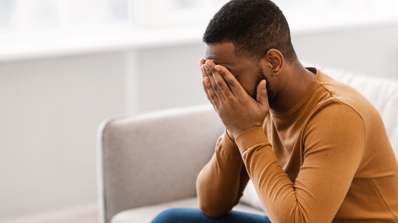 Depressed man sitting on couch covering his face