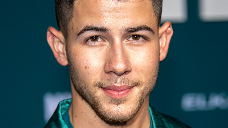 Nick Jonas wearing a green suit and posing at an event