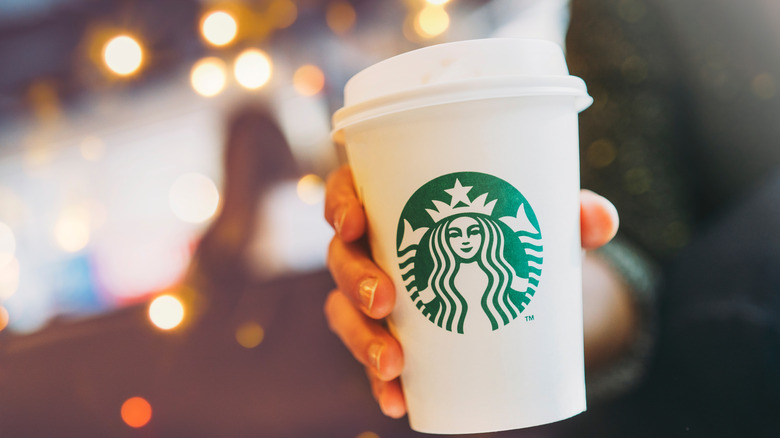 Person holding a white and green Starbucks cup