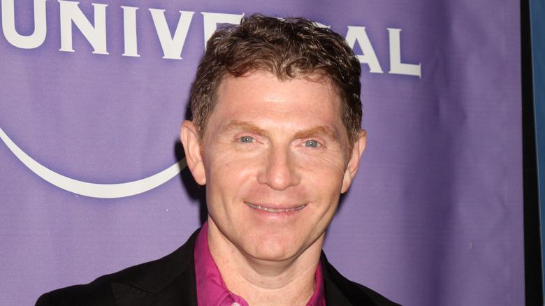 Bobby Flay wearing a purple shirt and black jacket