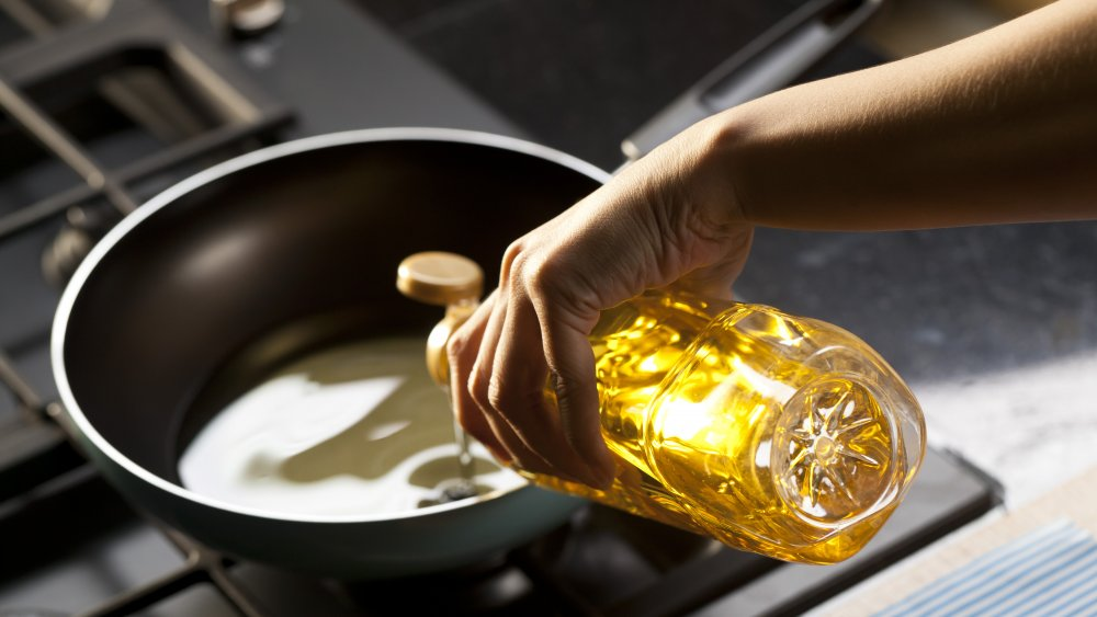 Pouring vegetable oil into a frying pan