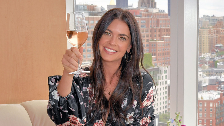 Katie Lee raising glass of wine with cityscape in background
