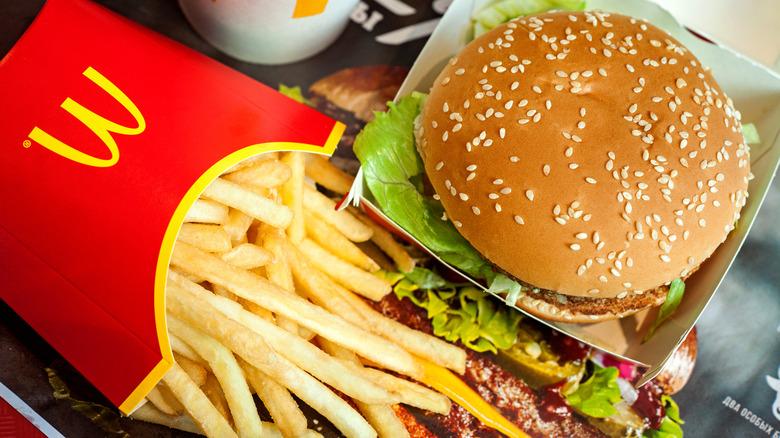Red box of McDonald's fries next to burger with sesame bun