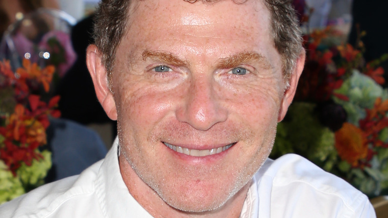 Bobby Flay wearing a white button down sitting and smiling