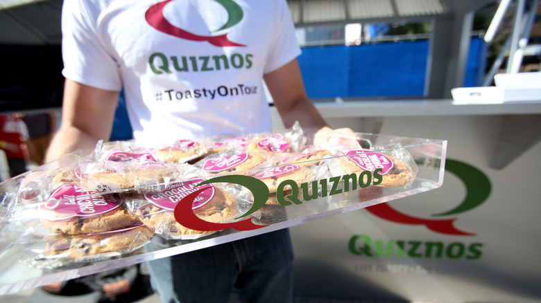 Man in Quiznos shirt carrying goodies from shop